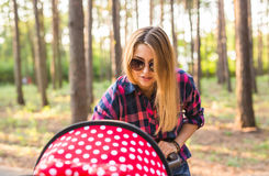 Closeup of mother with baby in pram walking in summer park Royalty Free Stock Photo