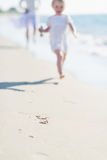 Closeup on mother and baby running along sea shore Stock Photos