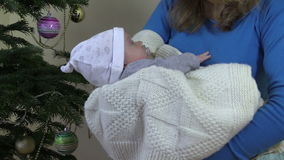 Closeup of mother cradle baby in hands near Christmas tree stock footage