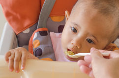 Closeup of mother feeding asian baby girl with a spoon in high c royalty free stock photos