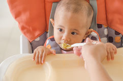Closeup of mother feeding asian baby girl with a spoon in high c royalty free stock photo