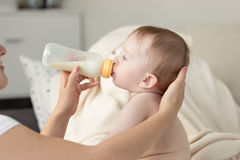 Closeup of mother giving milk from bottle to her baby son sittin Royalty Free Stock Photo