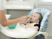 Closeup of mother giving porridge from spoon to her baby boy Royalty Free Stock Image