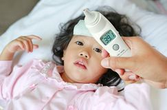 Closeup mother hand takes temperature for her daughter with high pressure of ear thermometer on bed at home stock images