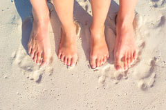 Closeup mother and kid feet on white sand beach Stock Image