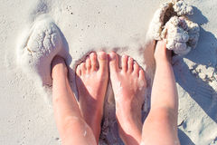 Closeup mother and kid feet on white sand beach Stock Images