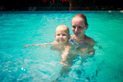 closeup mother small daughter swim smile in azure water of pool Royalty Free Stock Photos