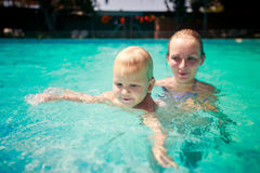 Closeup mother small daughter swim smile in azure water of pool Stock Photo