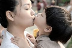 Closeup mother and son kissing together. Close up mother and son kissing together Royalty Free Stock Photo