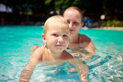 closeup mother teaches small daughter swim smile in azure pool Royalty Free Stock Photography