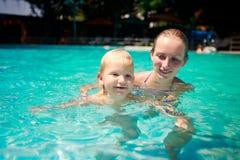 closeup mother teaches small daughter swim smile in azure pool Stock Photos