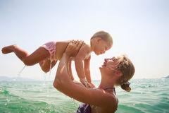 Closeup mother teaches swim small daughter in azure sea Royalty Free Stock Photography
