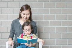 Closeup asian mother is teaching her son to read a book on stone brick wall textured background with copy space stock images