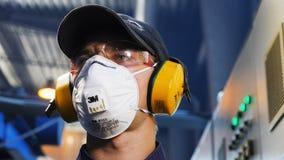 Closeup motion past employee in respirator and earphones