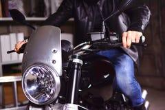 Biker is preparing to leave the garage on motorbike. Closeup of motorcycle headlamp. Biker is preparing to leave the garage royalty free stock photography