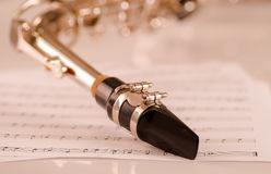 Closeup mouthpiece of saxophone lying on musical notes paper Stock Photography