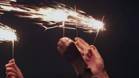 closeup Mouvement lent Bougies ou lumières de scintillement lumineuses du Bengale dans l'obscurité Fond fonc? de ciel Groupe heur banque de vidéos