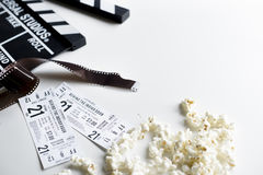 Closeup of movie tickets with popcorn and reels decoration on wh. Ite table Royalty Free Stock Photography
