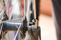 Closeup multi screwdriver working on mechanical parts next to wheel spokes Royalty Free Stock Image