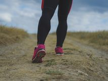 Closeup muscular legs. Man running on a blurred background. Running, jogging, walking concept. Sports lifestyle concept. Close-up picture of fit, sporty Royalty Free Stock Image