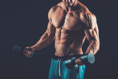 Closeup of a muscular young man lifting dumbbells weights on dar Royalty Free Stock Images