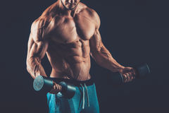 Closeup of a muscular young man lifting dumbbells weights on dar Royalty Free Stock Photos