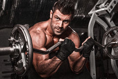 Closeup of a muscular young man lifting weights on dark backgrou Royalty Free Stock Photography