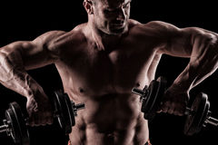 Closeup of a muscular young man lifting weights on dark backgrou. Close up of young muscular man lifting weights over dark background Royalty Free Stock Photo