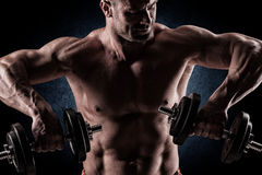 Closeup of a muscular young man lifting weights on dark backgrou. Close up of young muscular man lifting weights over dark background Royalty Free Stock Images