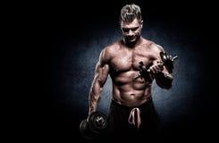 Closeup of a muscular young man lifting weights on dark backgrou Stock Photos
