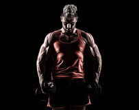 Closeup of a muscular young man lifting weights on dark backgrou Stock Photography