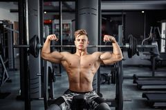 Close Up of a muscular young man lifting weights in gym on dark background royalty free stock photo