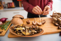 Closeup of mushrooms in a dish with woman stringing mushrooms Royalty Free Stock Image