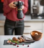 Closeup on mushrooms lingonberries and rosmarinus on table. And female food photographer in background Stock Image