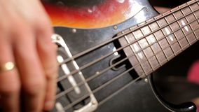 CloseUp of Musician Hands Playing Fast Music with Bass Guitar at the Concert. CloseUp of Bassist Playing Fast Music with Bass Guitar at the Concert in the stock footage