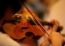 Closeup of the musician`s hand is playing a violin in an orchestra royalty free stock photos