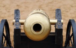 Closeup of muzzle of old metal cannon with wheel on sand Stock Photo