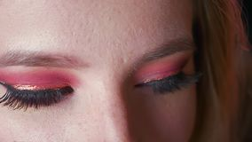 Closeup of mysterious stunning female blue eyes makeup with pink shadows and golden eyeline with the dark background.  stock footage