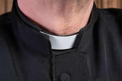 Priest clerical collar. Closeup of the neck of a priest wearing a black shirt with cassock and white clerical collar stock image