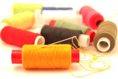 Yellow thread and needle Stock Images
