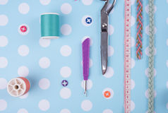 Closeup needles, thread spool, scissors, button on blue wooden Royalty Free Stock Images