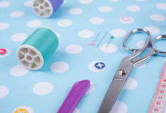 Closeup needles, thread spool, scissors, button on blue wooden Stock Photography