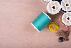 closeup needles, thread spool, scissors, button on wooden backgr Royalty Free Stock Photo