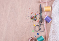 closeup needles, thread spool, scissors, button on wooden backgr Royalty Free Stock Image