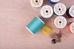 Closeup needles, thread spool, scissors, button on wooden Stock Photo