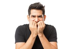 Closeup Of Nervous Young Man Biting Finger Nails. Against white background stock images