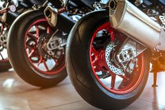 Closeup of new motorbike rear wheel . Big bike parked in showroom of dealership. Motorcycle exhaust pipes. Iconic motorcycle. With sports design. Black tire stock photography