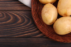 Closeup of new potatoes in a wooden plate, fresh tender vegetables for nutritious dishes on a dark brown background. Royalty Free Stock Photos
