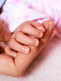 Closeup newborn baby holding his mothers finger Royalty Free Stock Image
