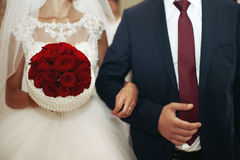 Closeup of newlywed couple holding hands and an elegant red rose Royalty Free Stock Images